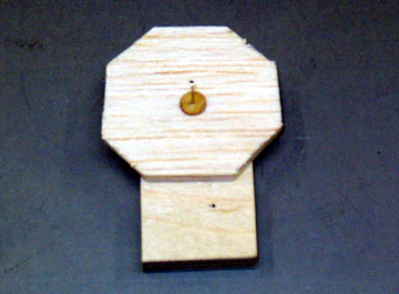 A dress-maker's pin holds the plug to a plywood base and allows the plug to be rotated.
