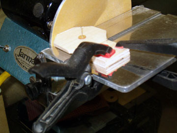 The base and plug are clamped to the disk sander.  The plug is rotated to shape it to a perfect circle.